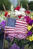 美国国旗和花在坟边 库存图片