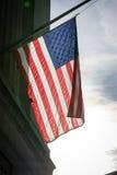 美国国旗特写镜头由后照的美国爱国心垂悬的背景 免版税库存图片