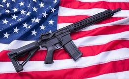 美国国旗表面,背景上的定制的AR-15马枪 美丽的夫妇跳舞射击工作室妇女年轻人 库存图片