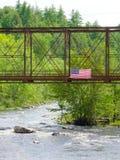 美国国旗飞行在一座老火车桥梁 免版税库存照片