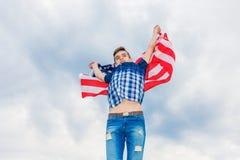 美国在夏天天空的背景中下垂由一个连续人举行 免版税库存照片