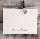 美国在扶手椅子的葡萄酒购物的纸袋 图库摄影