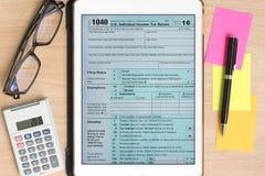 美国在片剂的报税表1040有计算器和笔的 免版税图库摄影