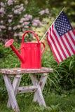 美国在红色喷壶下垂在庭院里 免版税图库摄影