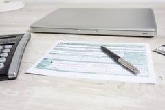 美国在闭合的计算机膝上型计算机、计算器和报税表旁边的报税表1040 报税表我们营业收益办公室 税天 免版税库存照片