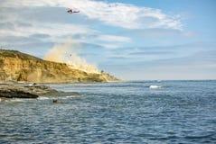 美国在飞行中海岸警备队直升机,与尘土的洛马角海滩 免版税库存照片