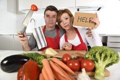 美国夫妇在烹调的围裙重音在家厨房里请求被挫败的帮忙 免版税库存图片