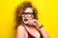 年轻美国女孩秀丽画象有卷曲发型的 摆在黄色背景的女孩,看照相机,微笑 工作室 库存图片