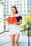 美国女性大学生阅读书,学习在校园里 图库摄影