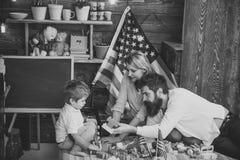 美国家庭和逗人喜爱的儿子使用与美国旗子 教儿子美国传统的父母使用,享受父母身分 库存照片