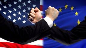 美国对欧盟交锋,国家分歧,在旗子背景的拳头 库存照片