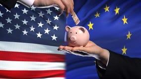 美国投资在欧盟,把金钱放的手中在piggybank在旗子背景,财务上 股票录像