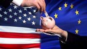 美国投资在欧盟,把金钱放的手中在piggybank在旗子背景,财务上 库存照片