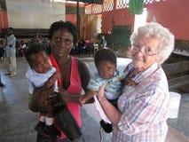 美国护士传教士拿着在农村海地的诊所的孪生 免版税库存照片