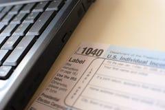 美国报税表1040和膝上型计算机 库存照片