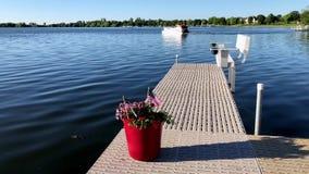 美国旗子和红色花在罐在小船船坞,当一艘浮船在一个美丽的Minnesota湖7月4日时通过  股票视频