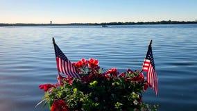 美国旗子和红色花在罐在小船船坞,当一艘浮船在一个美丽的Minnesota湖7月4日时通过  影视素材