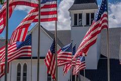 美国旗子挥动白色教会外在阵亡将士纪念日 库存照片