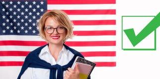 美国旗子背景的微笑的少妇 免版税库存照片