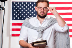 美国旗子背景的微笑的年轻人 免版税库存图片