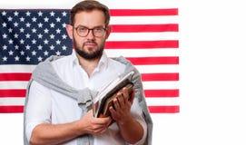 美国旗子背景的微笑的年轻人 免版税库存照片