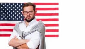 美国旗子背景的微笑的年轻人 图库摄影