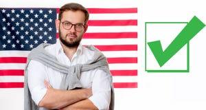 美国旗子背景的微笑的年轻人 库存图片