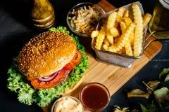 美国时髦的牛肉汉堡用烤肉和马约角服务用油炸物、凉拌卷心菜和啤酒 免版税库存照片