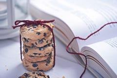 美国曲奇饼用在书旁边的巧克力 免版税库存图片
