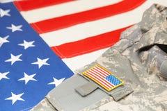 美国有V形臂章的军队制服在旗子 免版税库存照片