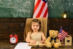 美国概念标志组人美国青年时期 有书的学生在反对美国旗子的公园 孩子需要 免版税图库摄影