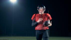 美国橄榄球运动员在与一个球的一个体育场领域走在手上 影视素材