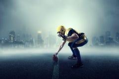 美国橄榄球运动员,在背景的都市风景 免版税库存照片