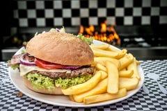 美国汉堡包用在火焰的炸薯条 免版税库存照片