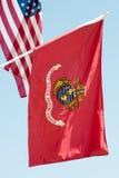 美国海军陆战队沙文主义情绪在蓝天背景,关闭,与美国国旗在背景中 库存图片