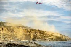 美国海岸警备队直升机在飞行中有尘土云彩的  免版税库存图片