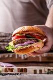 美国烹调的概念 从小圆面包、内容丰富的牛肉和猪肉炸肉排,蕃茄,黄瓜的一个人烹调的自创汉堡 库存照片