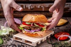 美国烹调的概念 从小圆面包、内容丰富的牛肉和猪肉炸肉排,蕃茄,黄瓜的一个人烹调的自创汉堡 免版税库存图片