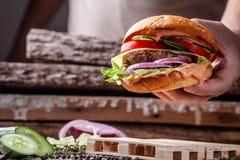 美国烹调的概念 从小圆面包、内容丰富的牛肉和猪肉炸肉排,蕃茄,黄瓜的一个人烹调的自创汉堡 免版税库存照片
