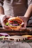美国烹调的概念 从小圆面包、内容丰富的牛肉和猪肉炸肉排,蕃茄,黄瓜的一个人烹调的自创汉堡 图库摄影