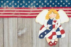 美国爱国老旗子和一个天使在被风化的木背景 免版税库存图片