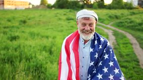 美国独立日7月第4 有一个灰色胡子和盖帽的领抚恤金者拿着美国国旗 美国人庆祝 股票录像