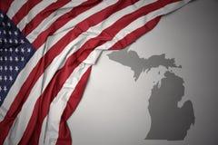 美国的挥动的国旗灰色密执安州的映射背景 库存照片