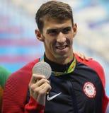 美国的迈克尔・菲尔普斯在奖牌仪式期间的在人里约的` s 100m蝴蝶以后2016奥林匹克 库存图片