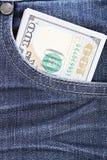 美国美元兑现在蓝色牛仔裤的口袋的金钱 免版税库存照片