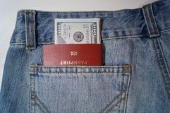 美国美元和外国护照在牛仔裤在白色背景装在口袋里 免版税库存照片