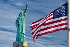 美国美国国旗星条旗在自由女神象蓝天背景 免版税库存图片