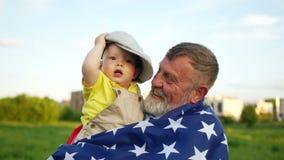 美国美国独立日,7月4日 祖父和小孙子庆祝美国独立日 盖帽的滑稽的婴孩,美国旗子 股票视频