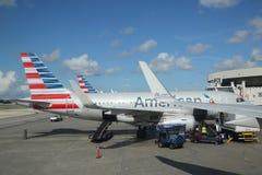 美国航空上载行李的行李管理者在迈阿密国际机场 免版税图库摄影