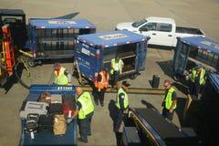 美国航空上载行李的行李管理者在迈阿密国际机场 免版税库存照片